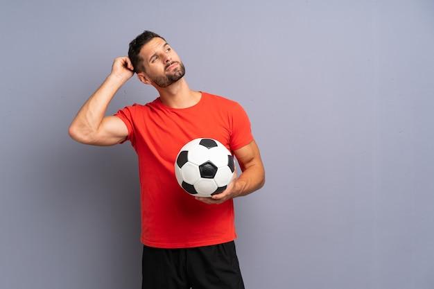 Knappe jonge voetbalstermens over geïsoleerde witte muur die twijfels hebben en met verwarren gezichtsuitdrukking