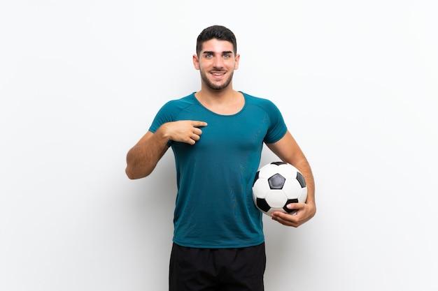 Knappe jonge voetbalstermens over geïsoleerde witte muur met verrassingsgelaatsuitdrukking
