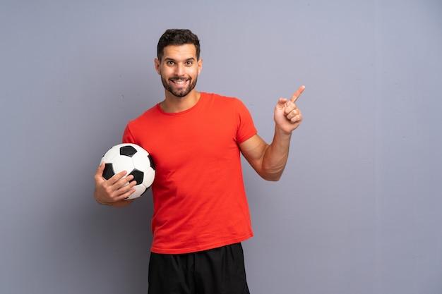 Knappe jonge voetbalstermens over geïsoleerde witte verrast muur en het richten van vinger aan de kant