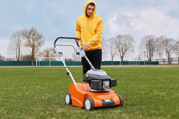 Knappe jonge volwassen mannelijke werknemer maaien veld met grasmaaier