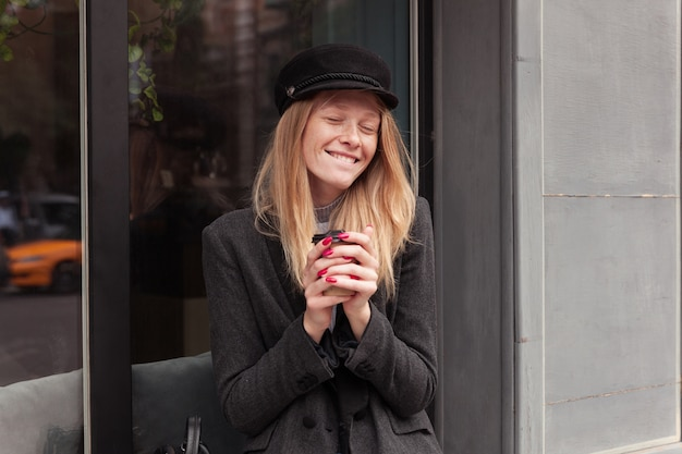 Knappe jonge vrolijke blonde vrouw met casual kapsel zittend op de vensterbank met kopje koffie en gelukkig lachend met gesloten ogen, gekleed in elegante grijze kleding