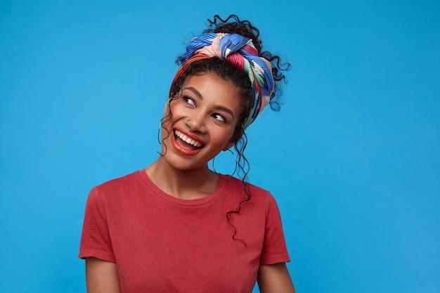 Knappe jonge vrolijke donkerharige krullende dame met verzameld haar in een hoge geest en gelukkig lachen, geïsoleerd over blauwe muur met handen naar beneden