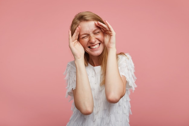 Knappe jonge vrolijke mooie roodharige vrouw met opgeheven handpalmen op haar gezicht en gelukkig lachend met gesloten ogen, staande tegen roze achtergrond in elegante blouse