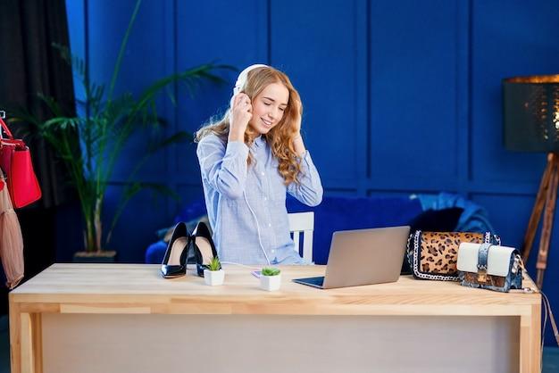 Knappe jonge vrouw het luisteren muziek in de hoofdtelefoon tijdens het opnemen van video.