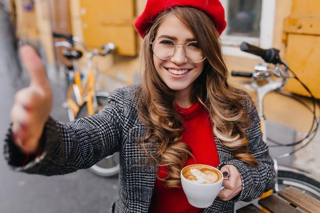 Knappe jonge vrouw in grijze jas koffie drinken met plezier op terras