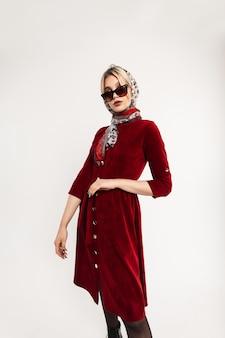 Knappe jonge vrouw in stijlvolle zonnebril in mooie luipaard sjaal op hoofd in rode mode jurk poseren in de buurt van witte vintage muur. fijne zakelijke blonde meisje model binnenshuis. sexy dame. retro.