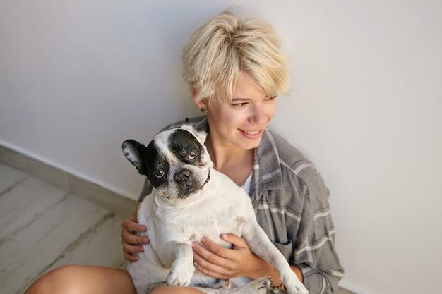Knappe jonge vrouw met blond haar poseren over interieur, zittend op de vloer met tevreden hond op haar handen, opzij kijkend met zachte glimlach