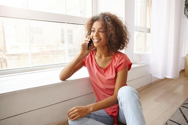 Knappe jonge vrouw met bruin krullend haar, leunend op de vensterbank met smartphone in haar hand, bellen en oprecht glimlachen, vrijetijdskleding dragen