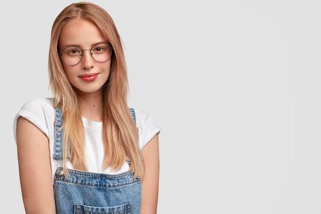 Knappe jonge vrouw met een tevreden gezichtsuitdrukking, heeft lang haar, een gezonde huid, draagt een ronde bril en een denim tuinbroek