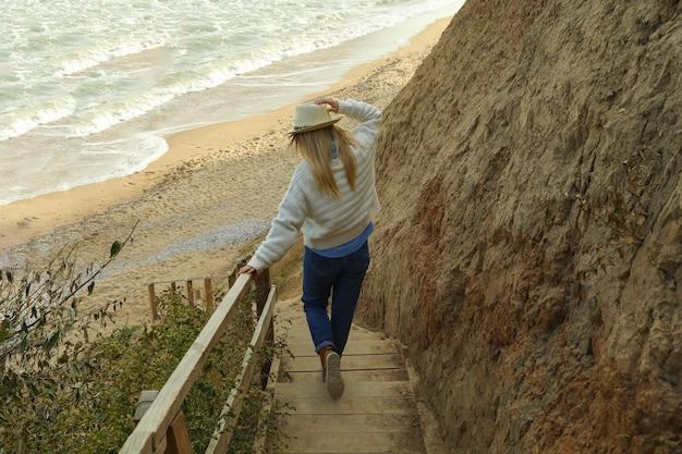 Knappe jonge vrouw op houten trappen tegen zandstrand