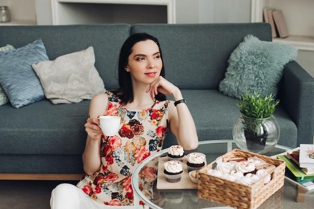 Knappe jonge vrouw zit op een verdieping en denkt aan iets en drinkt een hete thee woonkamer en denkt na over haar toekomst met een kopje koffie
