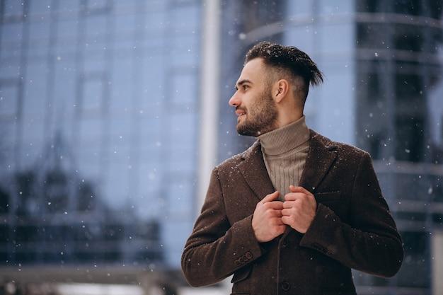 Knappe jonge zakenman buiten in de winter