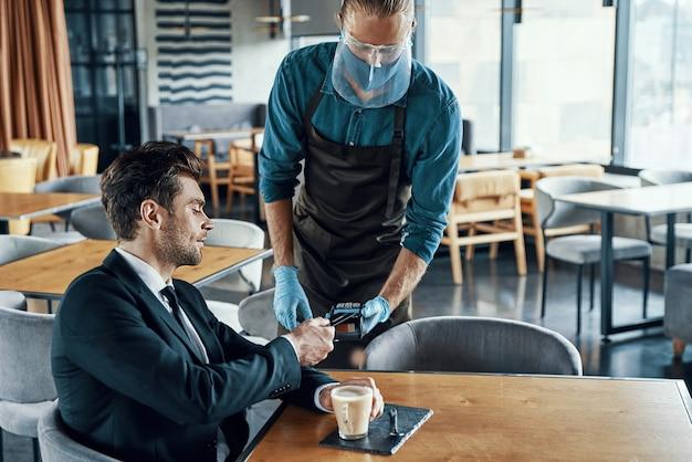 Knappe jonge zakenman die contactloos betaalt terwijl hij in het restaurant zit