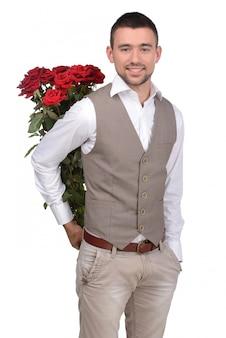 Knappe jonge zakenman die een bos van rode rozen houdt.