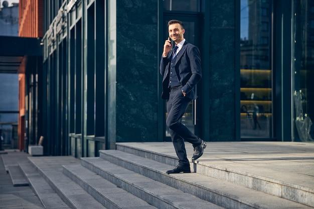 Knappe jonge zakenman die een modern groot kantoor verlaat en aan de telefoon praat terwijl hij vrolijk kijkt naar succes