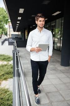Knappe jonge zakenman die in de stad loopt en tablet gebruikt