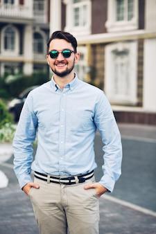 Knappe jonge zakenman die in zonnebril op straat loopt. hij houdt zijn handen in zijn zakken