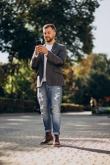Knappe jonge zakenman die telefoon buiten de straat gebruikt