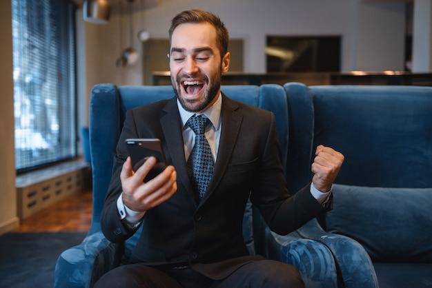 Knappe jonge zakenman draagt pak zit in de lobby van het hotel, met behulp van mobiele telefoon, succes te vieren
