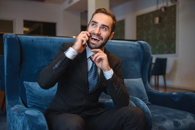 Knappe jonge zakenman draagt pak zit in de lobby van het hotel, met behulp van mobiele telefoon