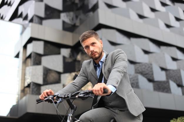 Knappe jonge zakenman fietsten buiten in de stad.