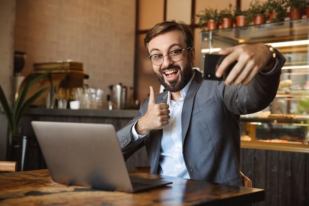 Knappe jonge zakenman gekleed in pak werkt op een laptopcomputer, zittend in het café binnenshuis, een selfie nemen