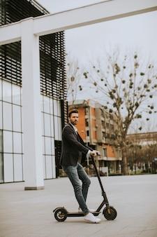 Knappe jonge zakenman in casual kleding rijden op een elektrische scooter door een kantoorgebouw op een zakelijke bijeenkomst