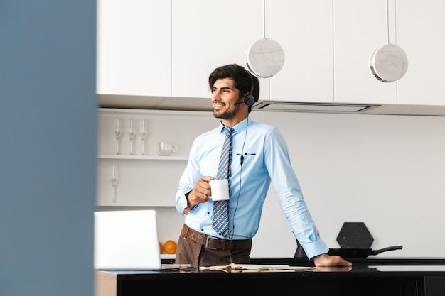 Knappe jonge zakenman in de keuken met behulp van lapto pcomputer met koptelefoon koffie drinken.