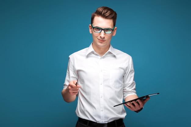 Knappe jonge zakenman in duur horloge, zwarte glazen en witte tablet en de pen van de overhemdsgreep