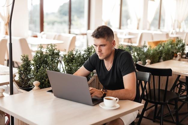 Knappe jonge zakenman in een stijlvol t-shirt met een laptop zit in een café en typen op een toetsenbord.