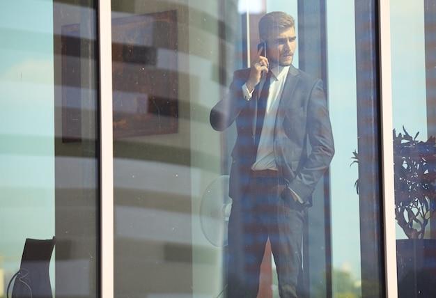 Knappe jonge zakenman in een stijlvolle, moderne kantoorruimte met grote ramen, praten aan de telefoon en naar buiten kijken