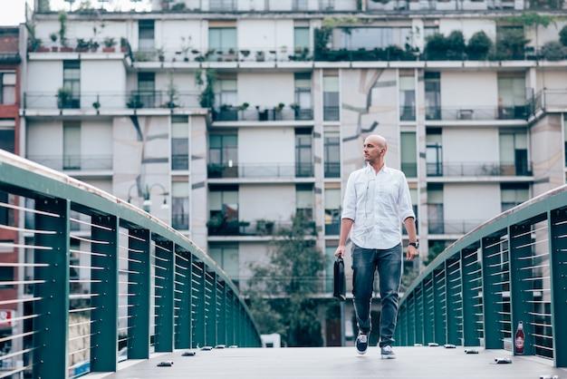 Knappe jonge zakenman in een wit overhemd dat een brug kruist