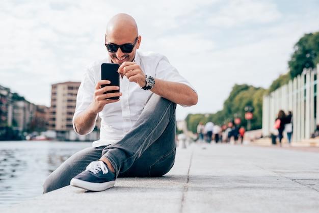Knappe jonge zakenman in een wit overhemd gezeten door het water met behulp van smartphone