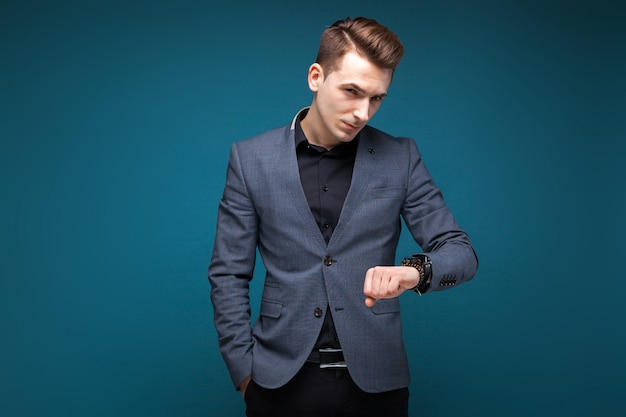 Knappe jonge zakenman in grijs jasje, duur horloge en zwart shirt