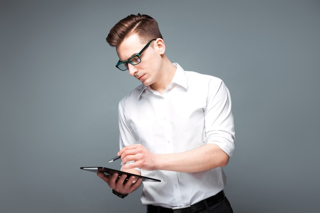 Knappe jonge zakenman in kostbaar horloge, zwarte glazen en witte overhemdgreeptablet en pen