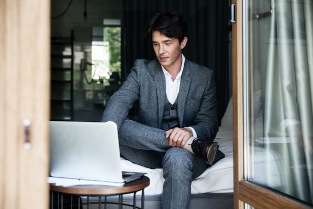 Knappe jonge zakenman in pak die op laptop werkt