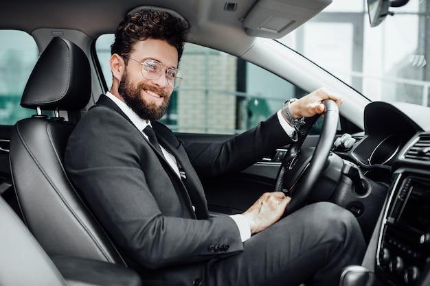 Knappe jonge zakenman in volledig pak glimlachend tijdens het rijden in een nieuwe auto