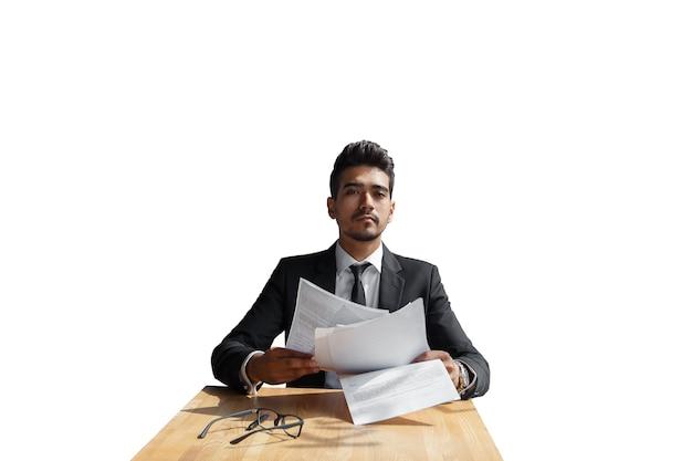 Knappe jonge zakenman met documenten in de hand geïsoleerd op witte achtergrond