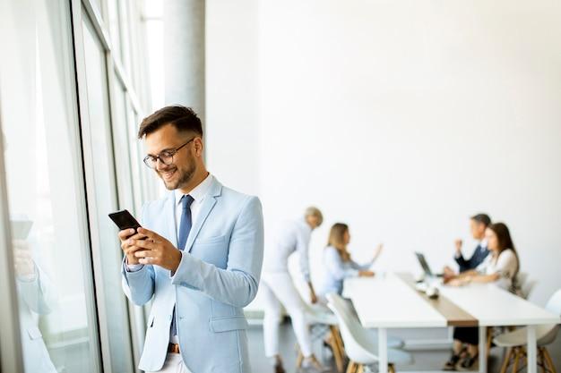 Knappe jonge zakenman met een mobiele telefoon op kantoor