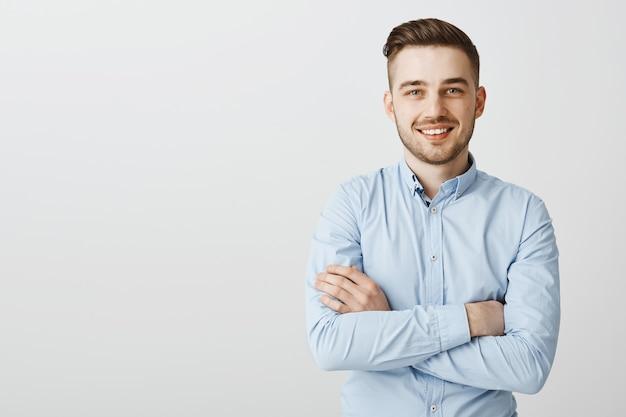 Knappe jonge zakenman met gekruiste armen glimlachend zelfverzekerd
