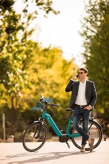 Knappe jonge zakenman op de ebike die mobiele telefoon met behulp van