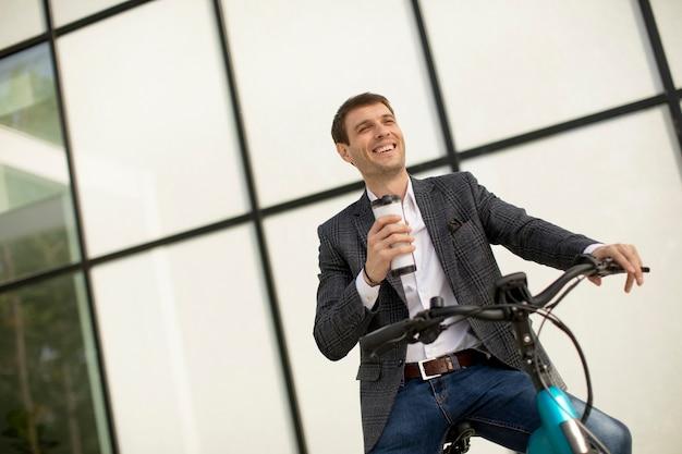 Knappe jonge zakenman op de ebike met afhaalmaaltijden koffiekopje