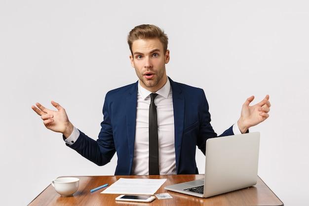 Knappe jonge zakenman verbaasd, kan niet begrijpen wat er gebeurt in bedrijf met werknemers die slecht werken, kantoor zitten met laptop, smartphone en documenten, handen zijwaarts gespreid verontrust