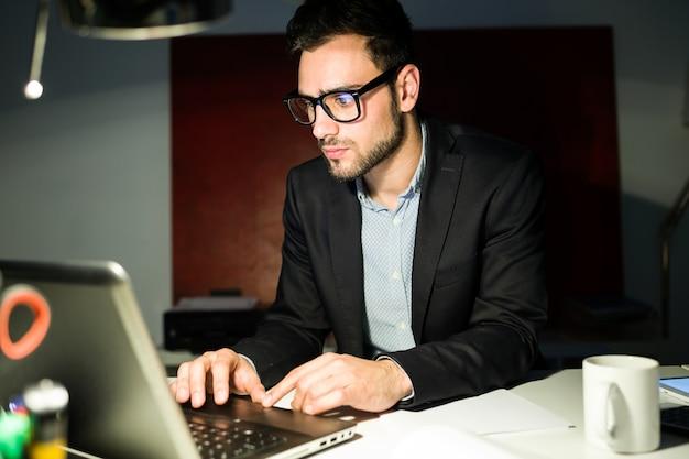 Knappe jonge zakenman werken met laptop in het kantoor.