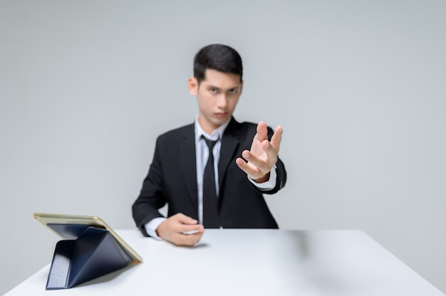 Knappe jonge zakenman zittend aan een tafel reiken zijn hand aan de voorkant terwijl hij uitkijkt.
