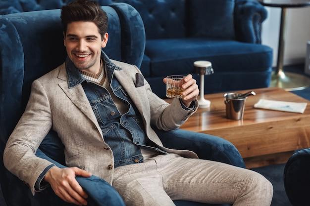 Knappe jonge zakenman zittend in stoel binnenshuis in kantoor alcohol drinken.