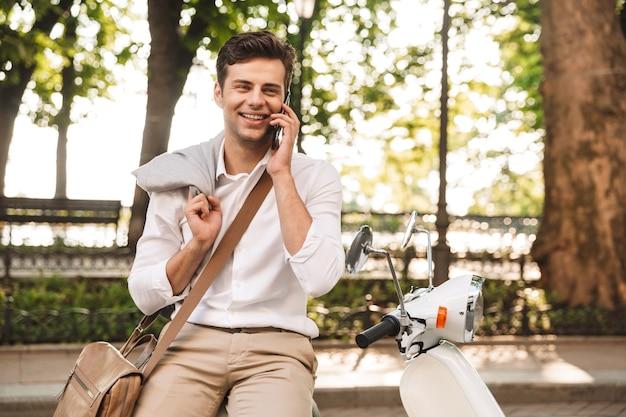 Knappe jonge zakenman zittend op een motor buitenshuis, praten op een mobiele telefoon