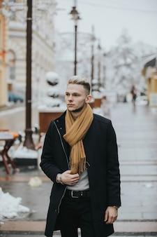 Knappe jonge zelfverzekerde man in een zwarte winteroutfit met een bruine sjaal die door de stad slentert