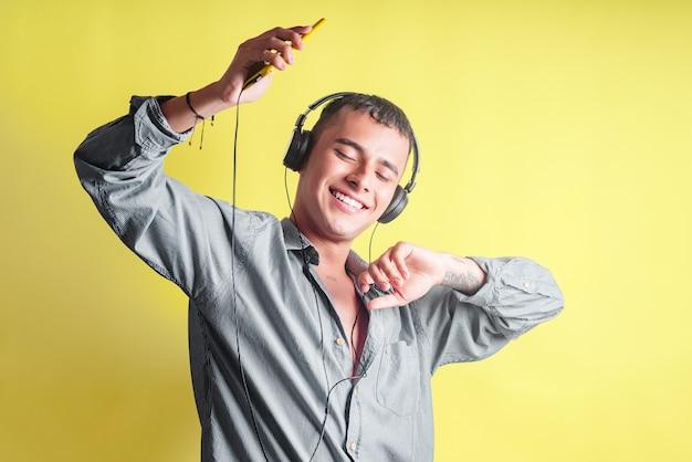 Knappe jongeman die danst terwijl hij naar muziek luistert op zijn mobiele telefoon op een gele studioachtergrond