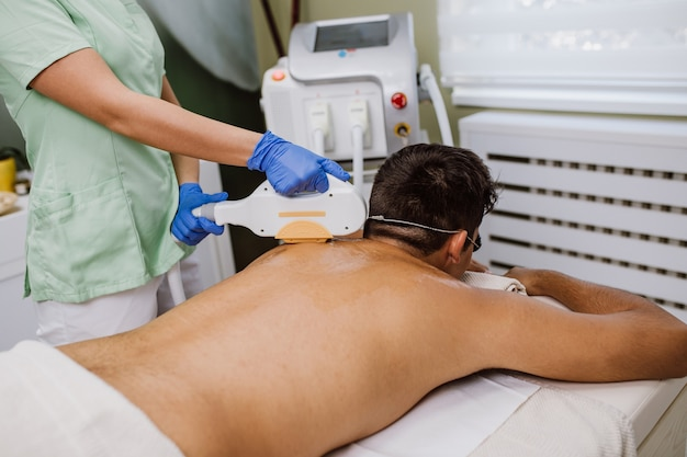 Knappe jongeman die de cosmetologieprocedure voor haarverwijdering op het gezicht krijgt in de cosmetische beauty spa-kliniek.